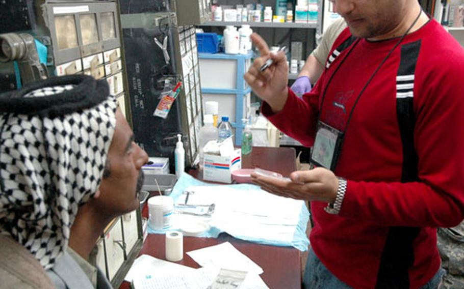 Dr. Firas Egal prescribes painkillers and antibiotics to an Iraqi suffering from kidney stones at Camp Scania's free clinic in southern Iraq on Friday.