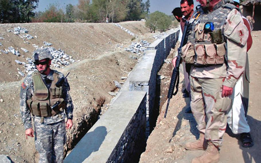 Capt. Christopher Corsten, left, examines a retaining wall on a road project in Jalalabad, Afghanistan. Corsten, with the Jalalabad Provincial Reconstruction Team, said the team focuses on projects, like roads, that will give locals the framework on which to rebuild the province themselves.