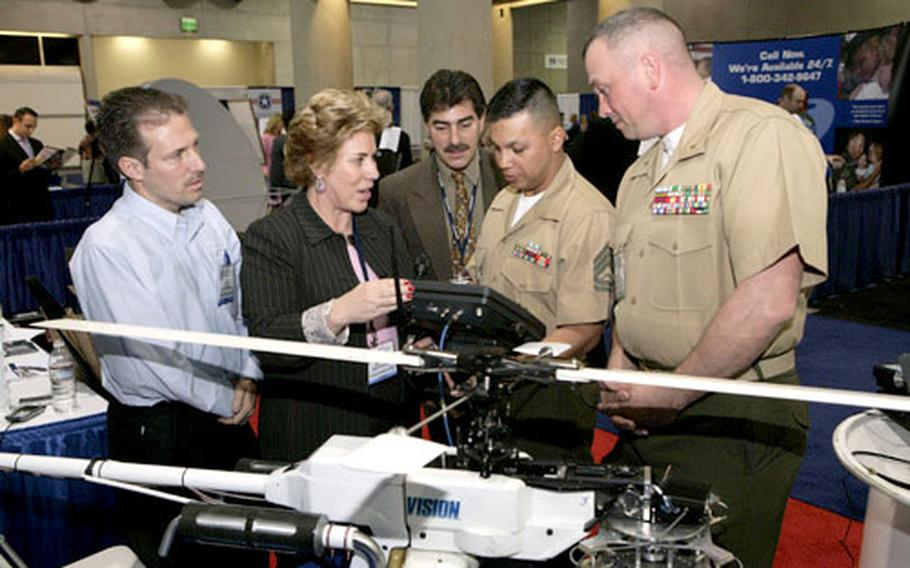 Chief Warrant Officer Michael Childs, right, Gunnery Sgt. Eulalio Ruiz III and others look at a gyro-stabilized platform after the Marines received the U.S. Naval Institute Copernicus Award in San Diego.
