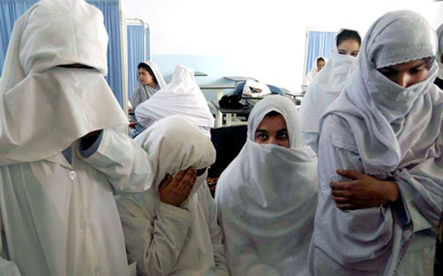 Student nurses at the new Qalat, Afghanistan hospital who trained at the local trade school established by the Qalat Provincial Reconstruction Team. In a very conservative area of Afghanistan, some of the girls are hiding their faces from the visiting coalition officers and cameras.