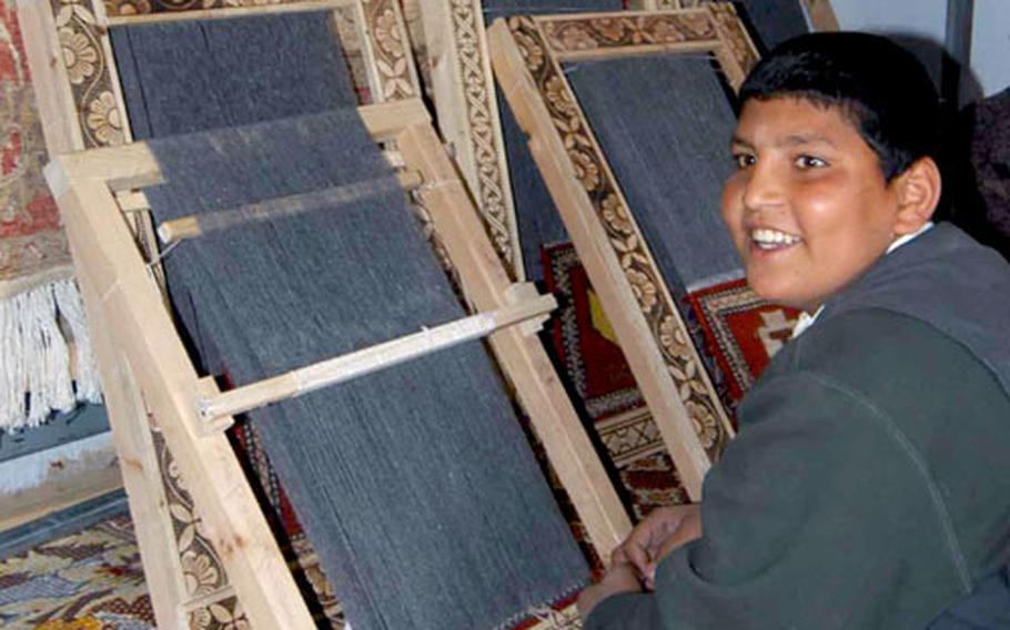A boy sits at his loom in the rug weaving class at the Qalat, Afghanistan trade school. After passing the class, the students can keep the looms to practice their trade. Currently, most of the rugs made are sold to soldiers stationed in the area.
