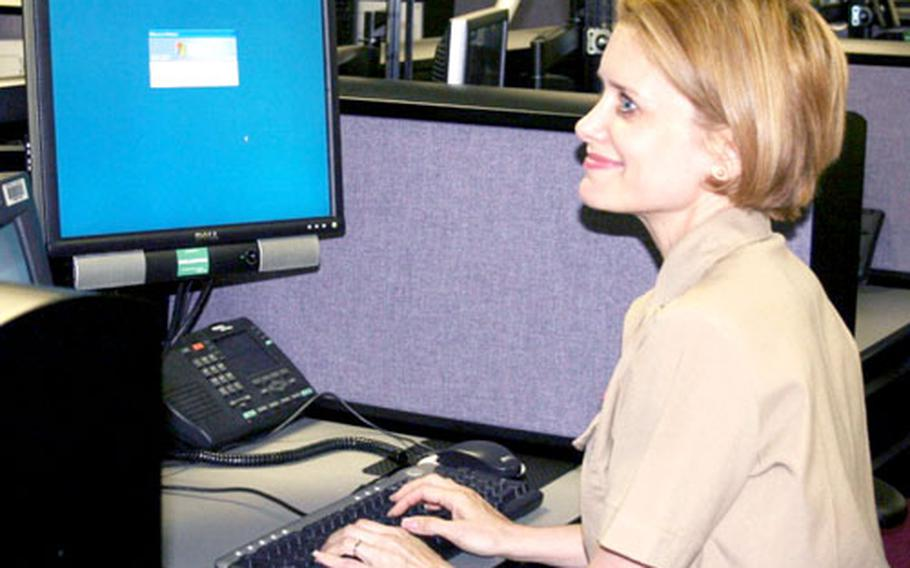Cmdr. Tina Van Hook Swallow, the Naval Computer and Telecommunications Station Far East commanding officer, works on the ONE-NET project — a massive migration to a centralized network for overseas shore-based Navy and Marine computers.