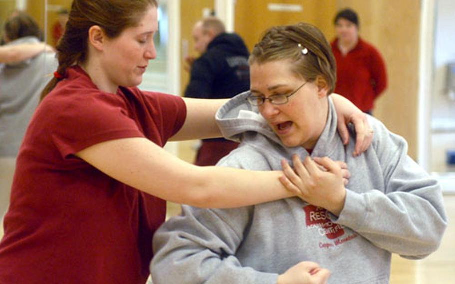 Maaret Ingram, right, practices an escape move on Camille Cruzan, during a women's self-defense class at RAF Mildenhall.