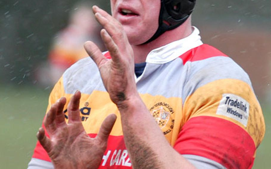Wearing headgear to protect his ears during scrums, Staff Sgt. Alf Thompson holds up his muddy arms as he prepares for a lineout play in a rugby match. Thompson, an RAF Lakenheath airman, plays for the Peterborough Rugby Club.