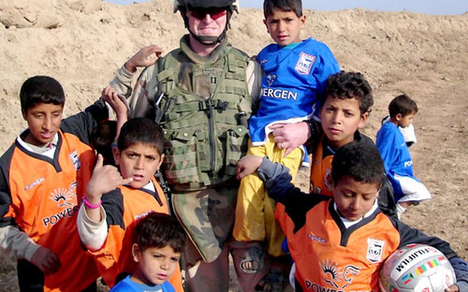 U.S. Army Capt. Mark Stoneman gathers with a group of Iraqi children after distributing soccer uniforms and gear to the youngsters.
