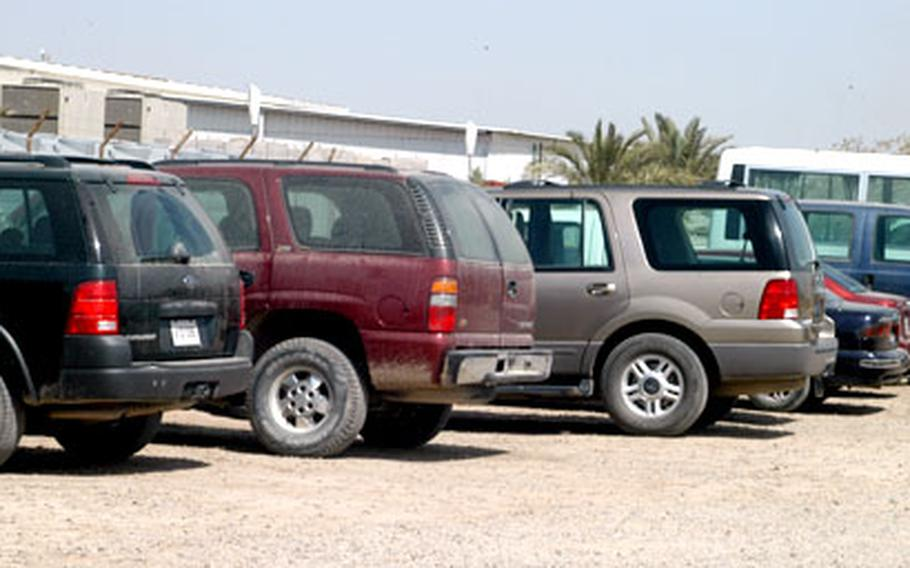 A Camp Victory dining facility lot is filled with SUVs at lunch. Some soldiers wonder why the vehicles are routinely used for on-base travel.