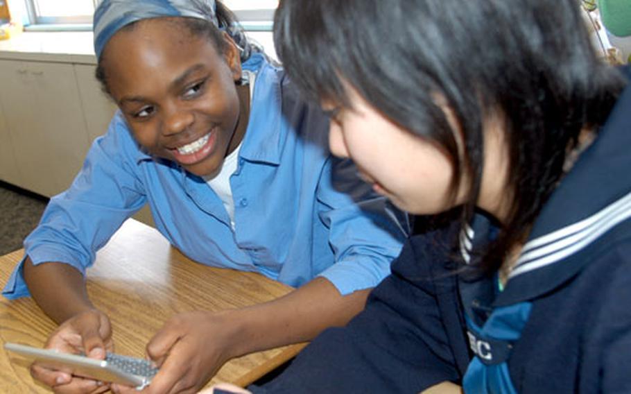 Kenya Jenkins, left, a ninth-grader at Edgren High School on Misawa Air Base, Japan, looks at a digital English-Japanese translator with Chisato Terashita on Tuesday.