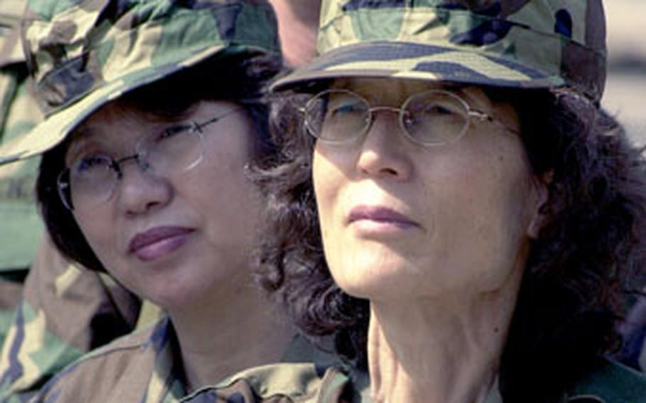 Civilian employees, decked out in camouflage uniforms, listen to a training session in Seoul on Tuesday.