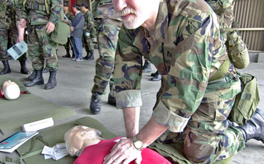 Ilmar Tarikas works on a training dummy at a first-aid station Tuesday in Seoul.