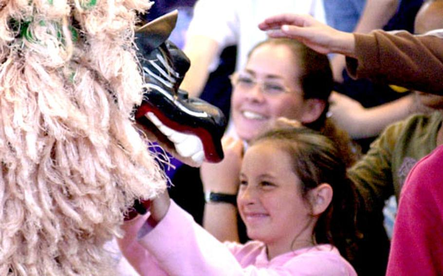 A Bechtel Elementary School student reaches out to pet a Shishi lion Tuesday as it enters the crowd after performing a dance.