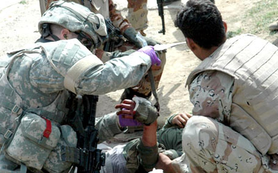 U.S. and Iraqi troops treat an Iraqi army soldier injured in a drive-by shooting in western Baghdad last week.