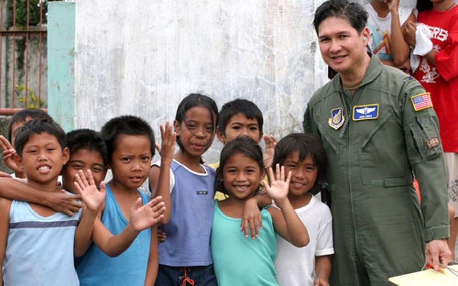 Air Force Col. John T. Cinco, a doctor, is greeted by several children in Saint Bernard in the Philippines on Feb. 23. Cinco, who was raised in the Philippines, is a member of a special international health unit Pacific Air Force maintains to assist in aid missions.