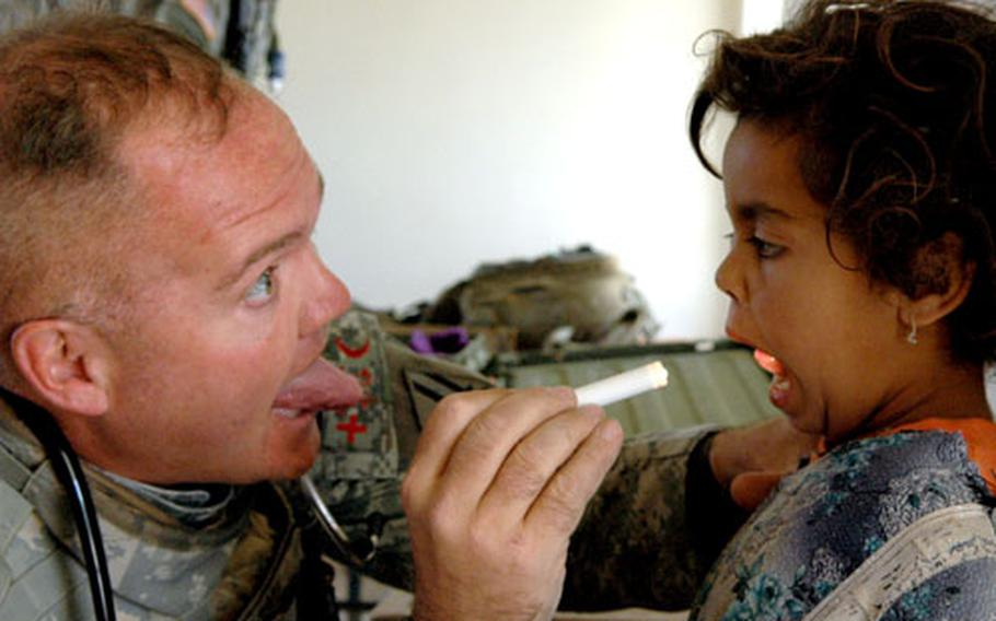 Medic Todd Cole asks an Iraqi girl to stick her tongue out during a medical exam during a civil affairs health mission near Camp Scania recently.