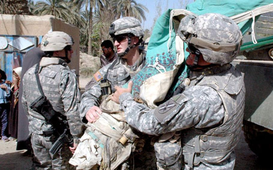 Capt. Rod Tatum with the 48th Brigade Combat Team helps unload a gift of tents during a civil affairs mission near Camp Scania recently. Tatum oversees public works projects such as the construction of water pumping stations, schools and medical clinics.