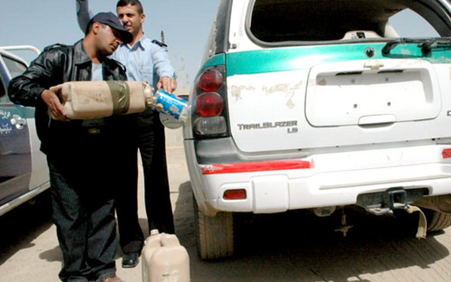 Iraqi police in the Rusala section of western Baghdad fill their trucks with gasoline provided by U.S. troops. Just getting out to patrol is a challenge for the Iraqi police force without sufficient gas.