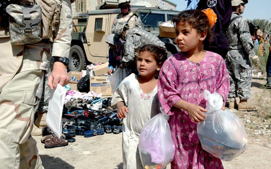 Two young girls collect gifts of humanitarian aid Saturday in southern Iraq.