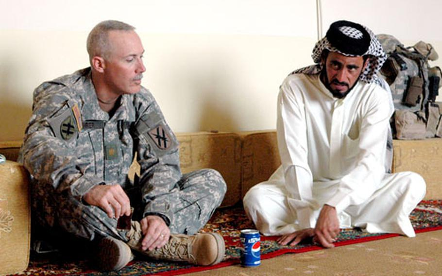 Maj. Joe Rohrer, left, meets with a local sheikh over tea and Pepsi in southern Iraq recently.
