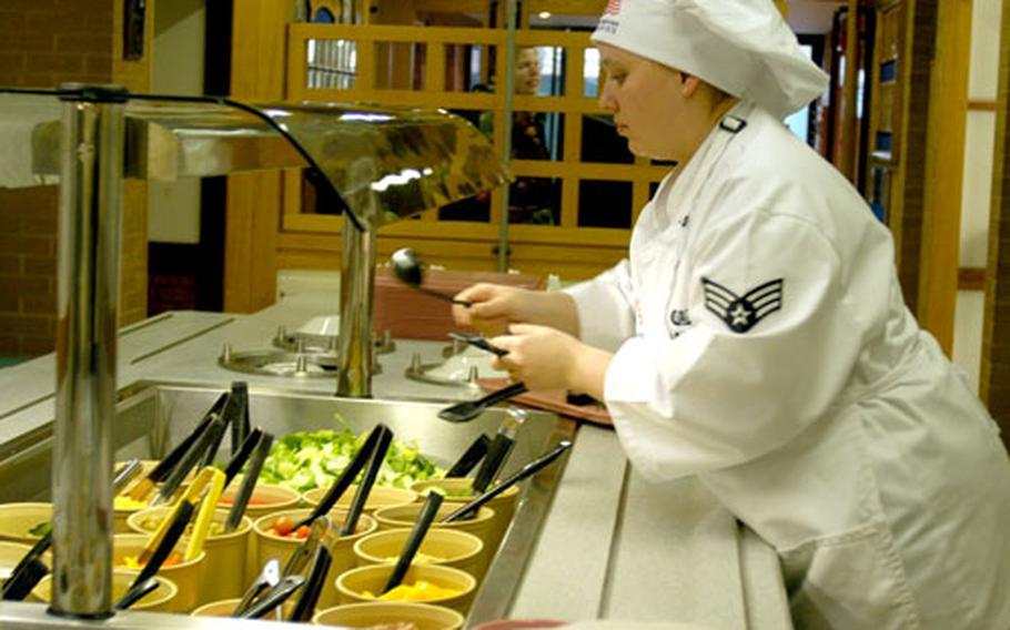 Airman 1st Class Tasha Marosi sets up the salad bar at the Knight's Table dining facility.