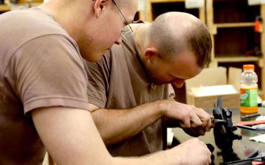 Pfc. Dustin Shugren, left, of St. Francis, Minn., and Spc. Kurtis King, of New Lexington, Ohio, both with the 322nd Maintenance Company, work on a weapon at the small-arms repair shop at Camp Anaconda, Iraq.