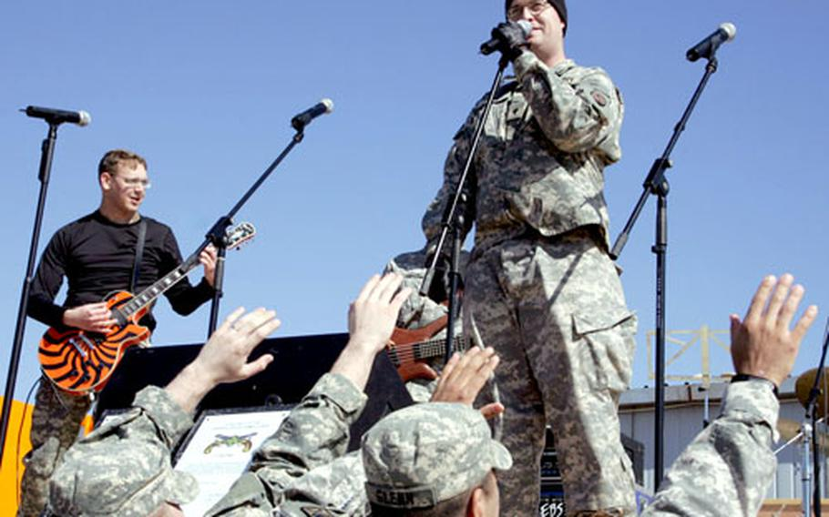 Spc. Jeffrey Long sings with V Corps rock band Article 15 on Feb. 13 during a performance for coalition troops, which included Slovaks, Poles, Mongolians, Romanians, Czechs and Albanians at Camp Echo in Diwaniyah. At left is guitarist Sgt. Terrel Henckel.