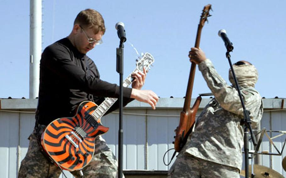 Sgt. Terrel Henckel, left, and Sgt. Stephen Edgerton entertain the troops at Camp Echo. Article 15's performacnes were the only outside entertainment the small camp had seen since August 2005.