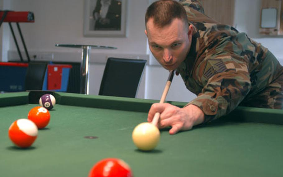 Master Sgt. Brian Bauer takes aim at a shot during a practice round at the RAF Lakenheath pool hall.