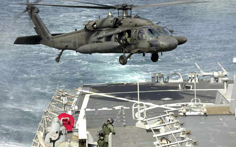 An Army UH-60 Black Hawk comes in for a landing on the back deck of the USS Curtis Wilbur during training Monday off the west coast of South Korea.
