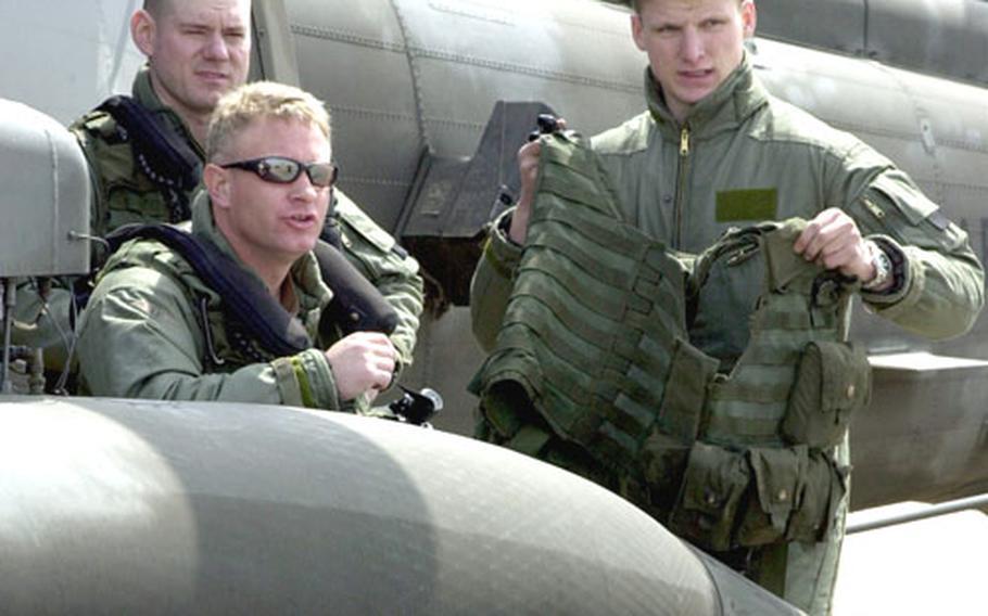 UH-60 Black Hawk crewmembers await deck landing qualifications aboard the USS Curtis Wilbur.