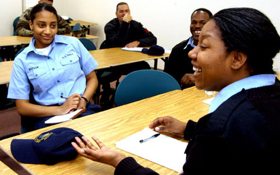 Petty Officer 1st Class Alisha Clifton chats with Seaman Jazmine Russell and Petty Officer 1st Class Antonio Arrington and other members of the Multicultural Committee meeting earlier this month.