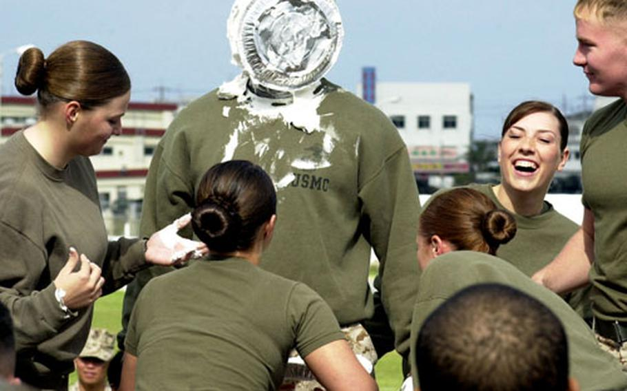 Marines from Combat Camera donated money to the Navy-Marine Corps Relief Society to earn the right to smother their former production chief, Staff Sgt. Keith Myrick, with whipped cream pies during Headquarters and Service Battalion's field day Wednesday on Camp Foster.