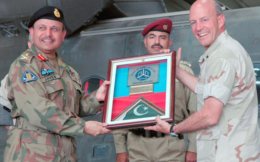Maj. Gen. Javed Aslam Tahir, commander of Pakistani Army Aviation, accepts a plaque from Navy Rear Adm. Michael LeFever, commander of the Combined Disaster Assistance Center, Pakistan, during a ceremony Thursday marking the departure of American servicemembers from Pakistan.