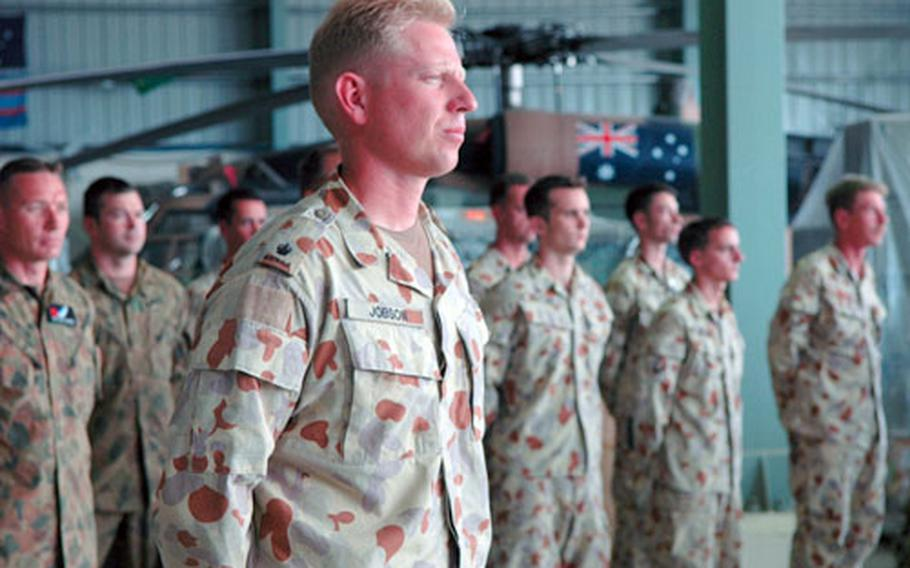 Australian soldiers stand next to an Australian BlackHawk Thursday during a ceremony marking the departure of American and Australian servicemembers from Pakistan. The Australian Army's four BlackHawks performed the majority of military personnel transportation for the relief effort.