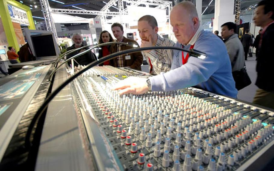 Visitors to the trade show check out an Altair Audio soundboard used for mixing audio from live shows as well as in a recording studio.