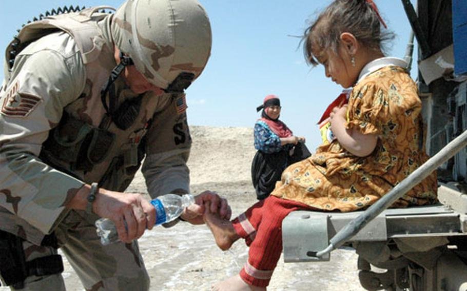 Tech. Sgt. Jeffrey Fort, 33, of Florissant, Mo., an Air Force patrol leader, treats a local child for cuts on her feet during a recent patrol outside Ali Base in Iraq.
