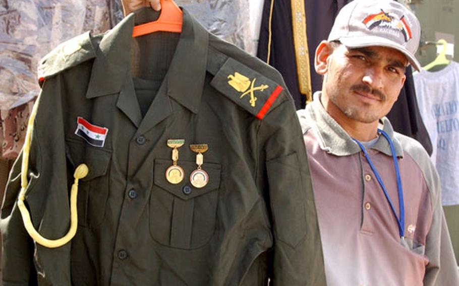 An Iraqi vendor shows off a military uniform from Saddam Hussein's army, an example of a war souvenir U.S. troops can take home, if they have a receipt.