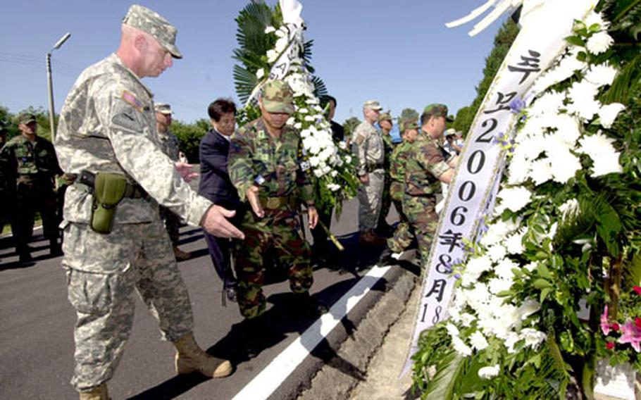 Command Sgt. Maj. Daniel P. Ciarrocchi, left, of the United Nations Command Security Battalion–Joint Security Area, assists in placing wreaths on a memorial for two U.S. soldiers killed in the JSA during an Aug. 18, 1976, attack. The security battalion hosted a memorial ceremony for the soldiers Friday.