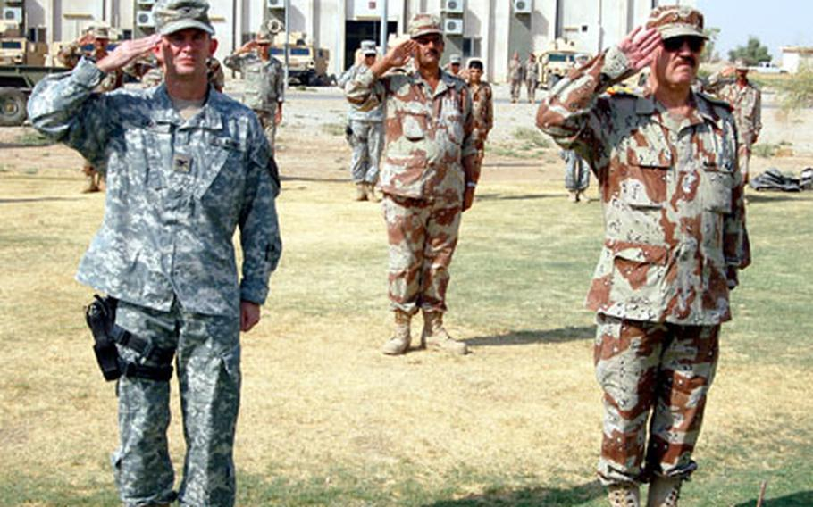 Army Col. David R. Gray, left, commander of the 1st Brigade Combat Team, 101st Airborne Division, and Maj. Gen. Anwar, commander of 2nd Brigade, 4th Iraqi Army, salute during a transfer of authority ceremony at Kirkuk, Iraq, on Friday.