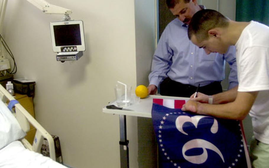Romanian Staff Sgt. Larentiu Serban, who lost a leg as a result of a land mine in Afghanistan, signs a Flight 93 memorial flag Thursday at Landstuhl Regional Medical Center, Germany.