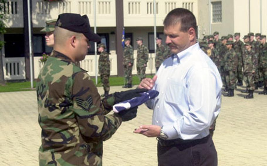 Air Force Staff Sgt. Ubaldo Barrios with the Ramstein Air Base Honor Guard presents Ken Nacke with a Flight 93 memorial flag Thursday afternoon at Kapaun Air Station, Germany.
