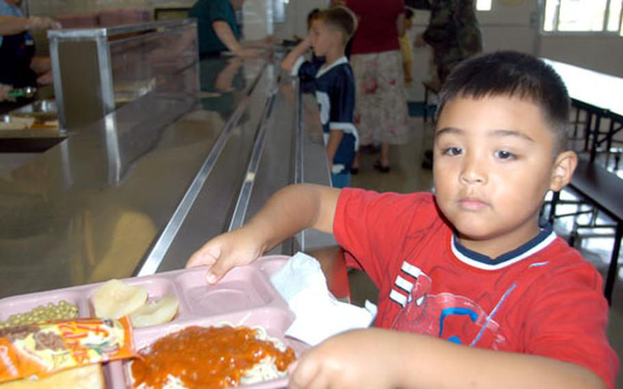 First-grader Phil Araneta grabs his lunch tray and finds a seat at Cummings Elementary School at Misawa Air Base, Japan, last year. Spaghetti is still in, but peas are off the menu at DODDS schools.