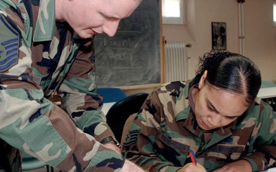 Master Sgt. James McGee, left, helps Staff Sgt. Jennifer Manamea-Nelson fill out her Registration and Absentee Ballot Request at Rhein-Main Air Base, Germany, in Aug. 2004.