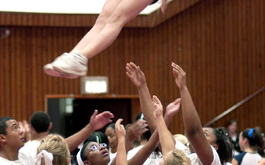 Holly Bellamy, a senior at Ramstein High School in Germany, is tossed aloft during stunt training at cheer camp on Friday.