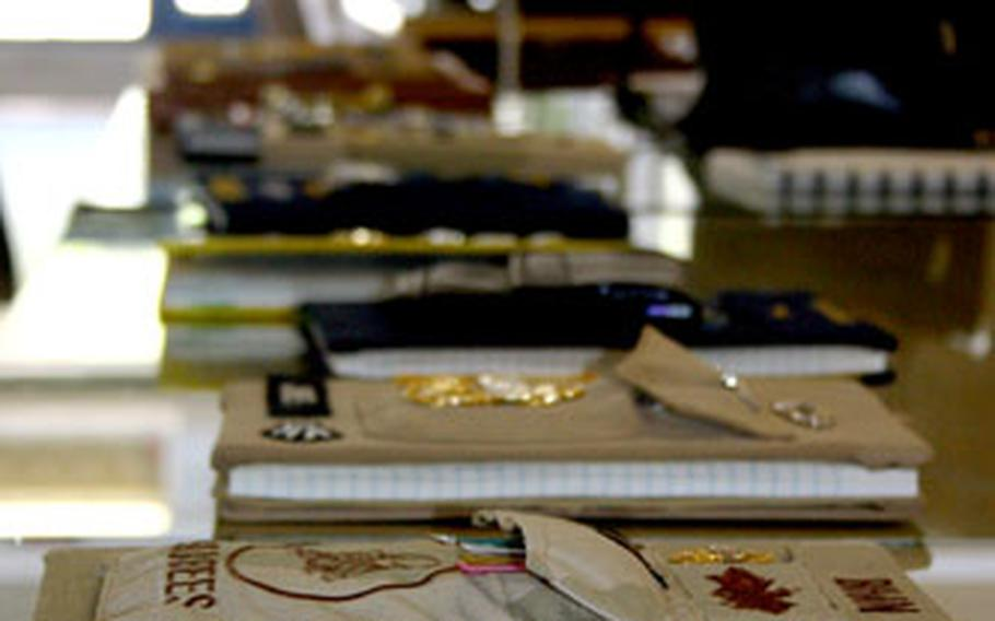 """An enduring tradition of the promotion from E-6 to E-7 in the Navy includes the keeping of a """"charge book."""" One after another, selectees' decorated charge books stretched across a cafeteria table at the Naval Station Rota, Spain, CPO academy site on Camp Mitchell. Inside, presumably, are words of wisdom chiefs penned to their understudies."""