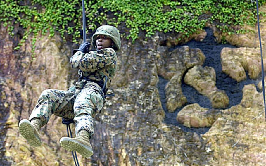 Lance Cpl. Ebony Rhodes, 21, from Houston, with 3rd Materiel Readiness Battalion on Camp Kinser, performs her first controlled break after stepping off the lip of the skid, a platform that simulates the back of a helicopter, at the rappel site on the Jungle Warfare Training Center Thursday.