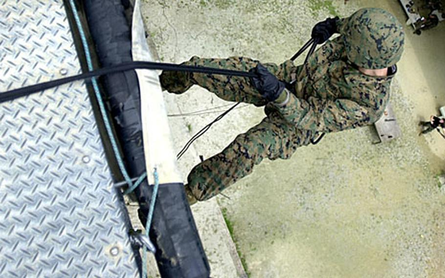 3rd MRB Lance Cpl. Louis Ocampo, 19, from New York, with 3rd Materiel Readiness Battalion, steps off the lip of the skid at the Jungle Warefare Training Center Thursday.