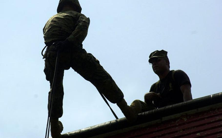 Lance Cpl. Louis Ocampo (left), 19, New York, with 3rd Materiel Readiness Battalion, moves into an L-shaped position against the wall as helicopter rope suspension training master Sgt. Benjamin Luna offers some final instructions at the rappel site at the Jungle Warfare Training Center Thursday.