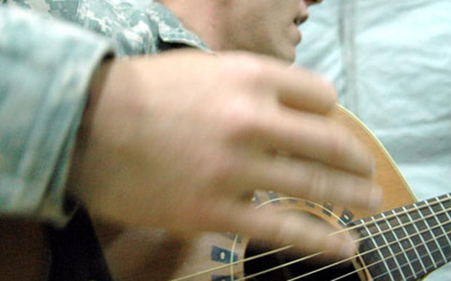 """Joshua Revak, singer of """"The Bandit Song,"""" practices his guitar and vocals while he was deployed to Camp Nimur in northwest Iraq earlier in the year. Revak, who has recorded numerous songs about fallen comrades and life in Iraq, said he has lost inspiration to sing and play after the death of his mentor, 1st Sgt. Aaron Jagger."""
