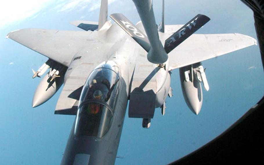 An aerial refueling boom delivers fuel from a KC-135R Stratotanker to an F-15E Strike Eagle jet fighter during an air refueling mission Aug. 30.