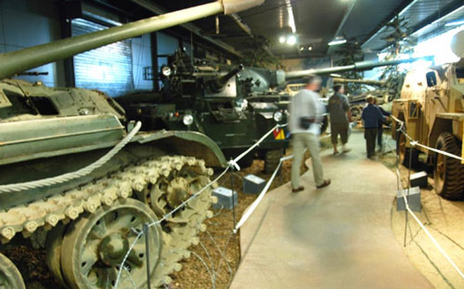 Visitors wander among the treads and turrets of some of the more modern machines of war on display.