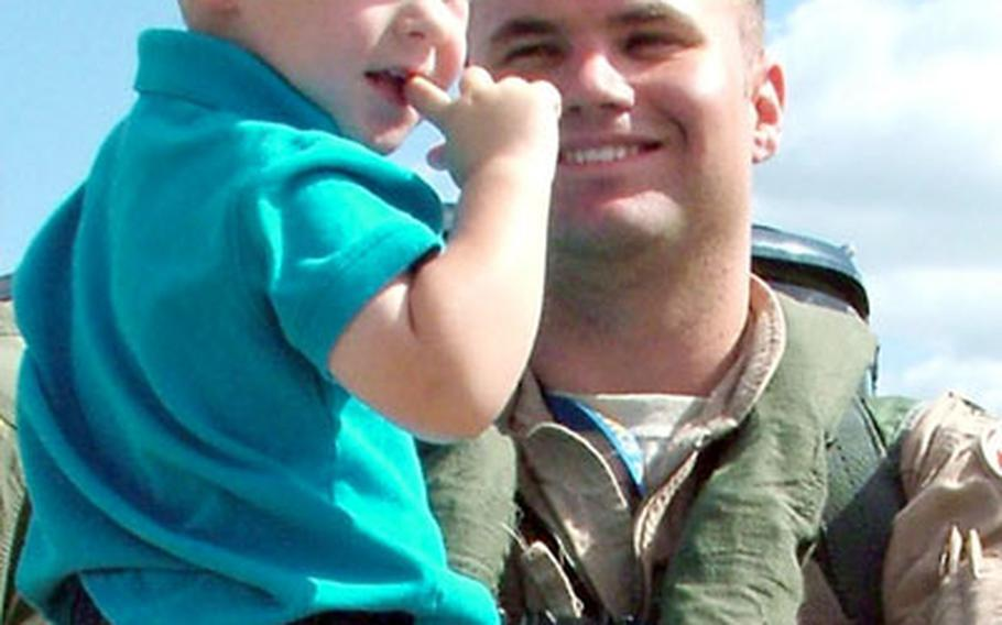 Capt. Matt Lande holds his son Nick, 2, after arriving at Spangdahlem Air Base, Germany, on Monday. The F-16 pilot with the 23rd Fighter Squadron was one of six pilots who returned home after a two-month deployment to provide close-air support to troops in Iraq and Afghanistan. The rest of the squadron will return home in the next week.